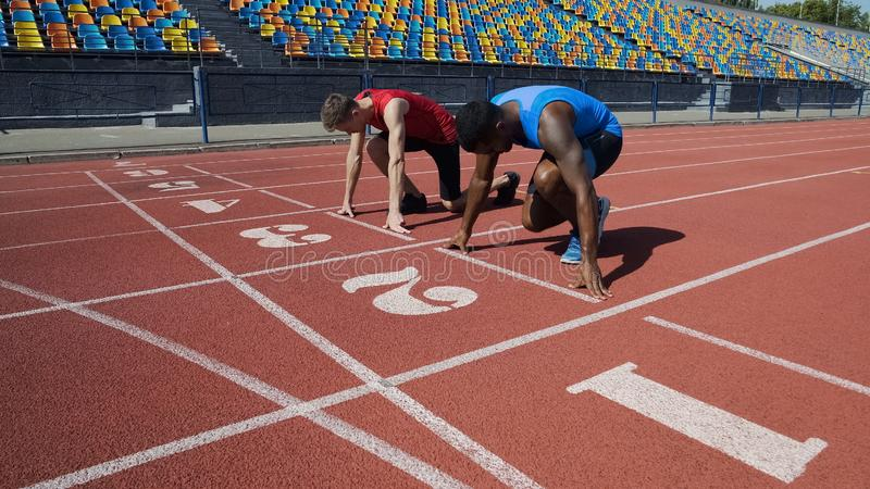 Two multiracial athletes in starting position, ready to run after command stock image
