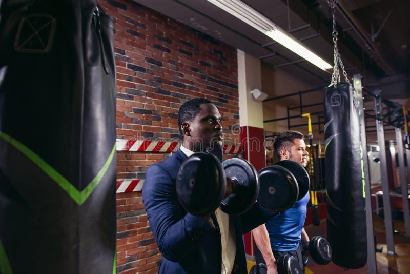 Two muscular men doing biceps workout. royalty free stock photo