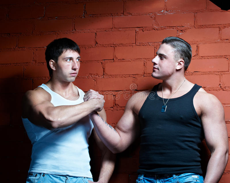 Two muscular guys. Two handsome young guys with big muscles stock photography
