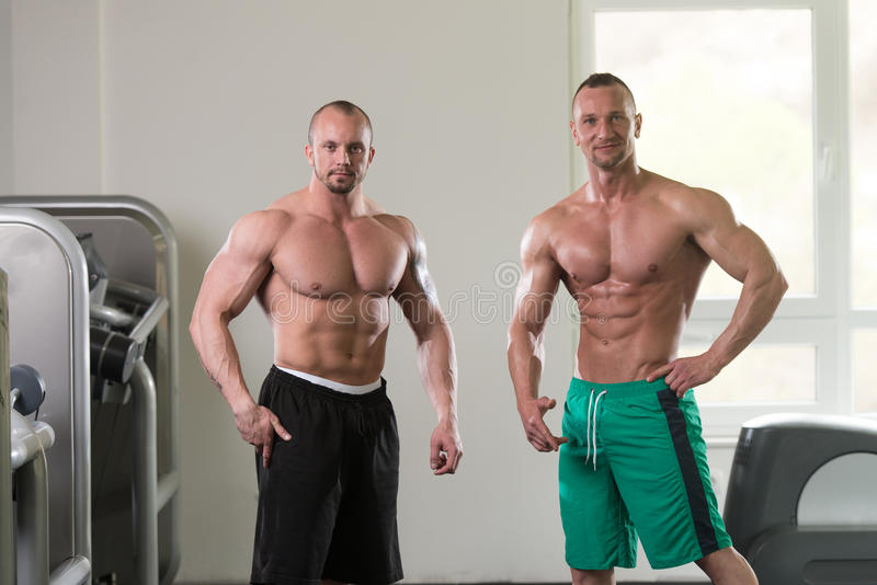 Two Muscular Men Flexing Muscles In Gym stock photos