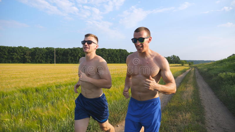Two muscular men running and talking outdoors. Young athletic guys jogging over the field. Male sportsmans training stock photo