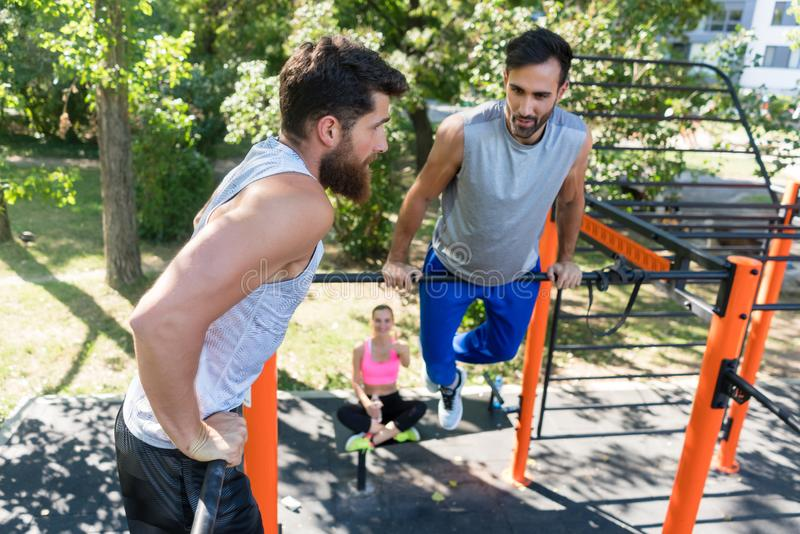 Two muscular young men doing bodyweight exercises in a modern fi royalty free stock photos