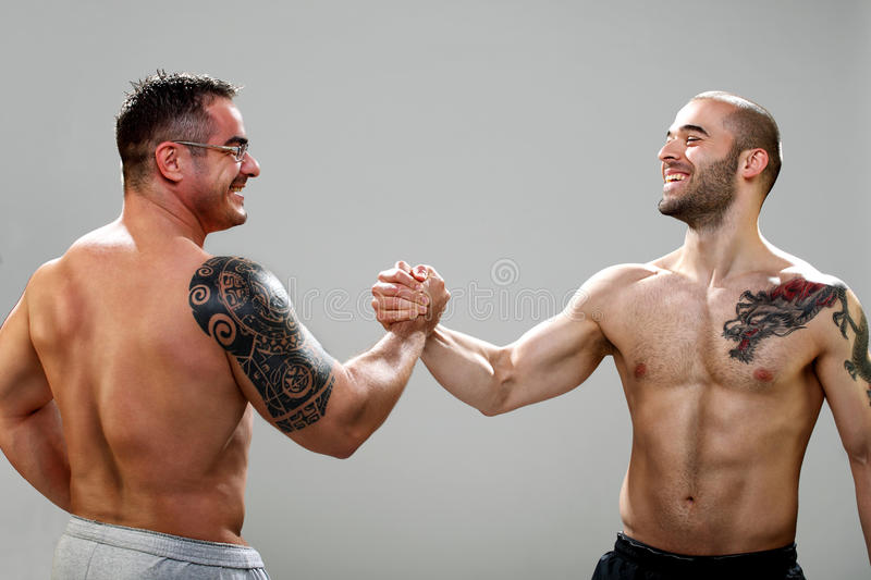 Two musculine happy guys making an agreement stock image