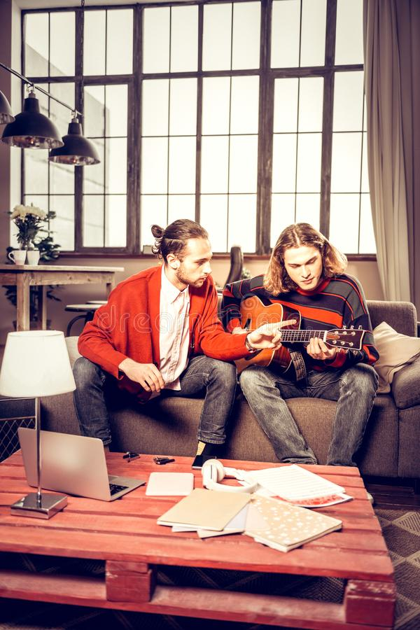 Two musicians playing in the band composing new song at home stock images