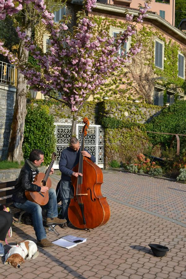 Two musicians playing guitar and contrabass at the Varenna lakefront in a sunny spring day. Varenna/Italy - April 6, 2014: Two musicians playing guitar and royalty free stock photography