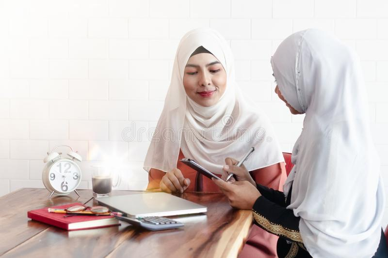 Two Muslim women doing business together. Two young Asian Muslim women doing business together. The seller is writing down the order that the customer wants to royalty free stock image