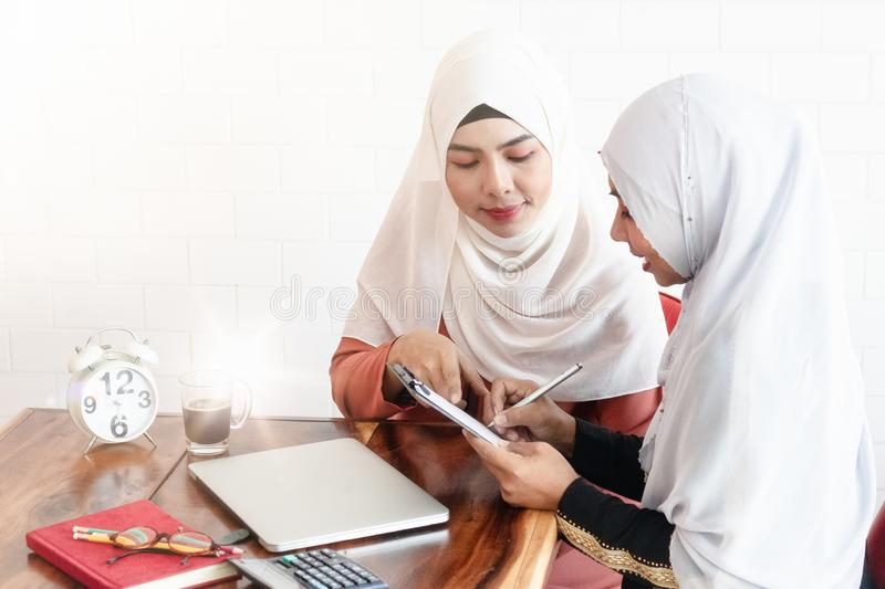 Two Muslim women doing business together. Two young Asian Muslim women doing business together. The seller is writing down the order that the customer wants to stock photos