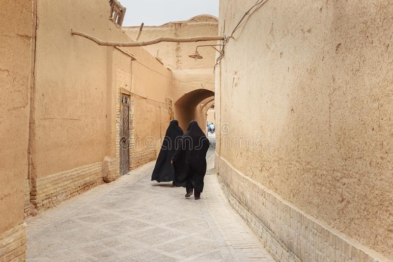 Two Muslim women, dressed in black chador walk on the narrow street of old town in Yazd. Iran. Yazd, Iran - March 23, 2018: Two Muslim women, dressed in black stock photos