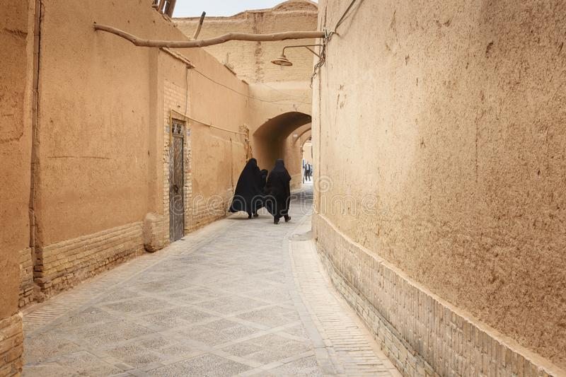 Two Muslim women, dressed in black chador walk on the narrow street of old town in Yazd. Iran stock image
