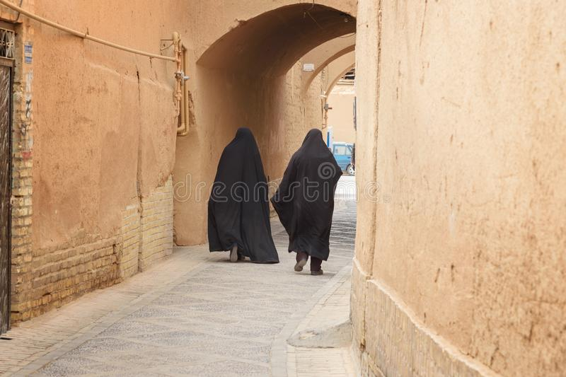 Two Muslim women, dressed in black chador walk on the narrow street of old town in Yazd. Iran stock photo