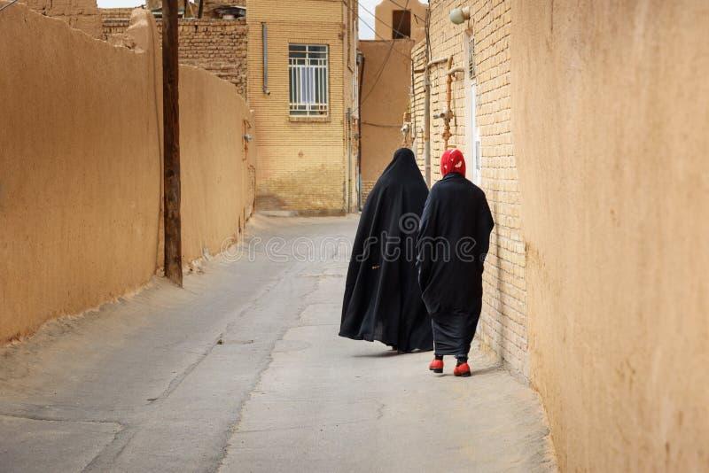 Two Muslim women, dressed in black chador walk on the narrow street of old town in Yazd. Iran. Yazd, Iran - March 23, 2018: Two Muslim women, dressed in black stock image
