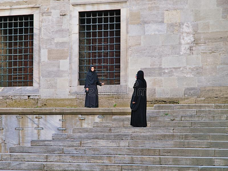 Two muslim women  one taking picture, one posing royalty free stock photos