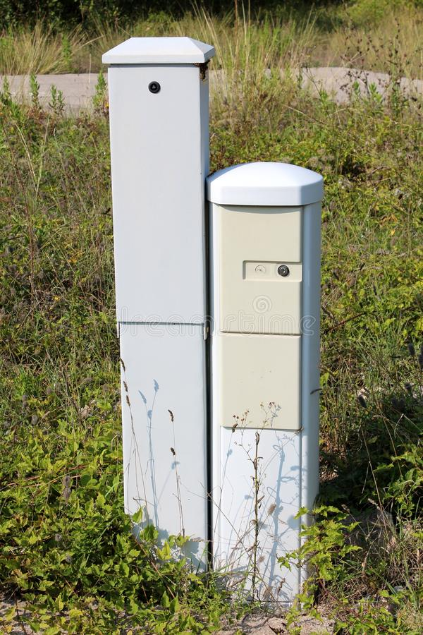Two narrow tall light grey locked electrical boxes surrounded with tall uncut grass and other vegetation at abandoned industrial royalty free stock photos