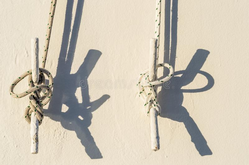 Two nautical ropes tied to metal cleats on wall of cruise ship. Two nautical ropes tied with marine knots to metal cleats on white exterior wall of cruise ship stock images
