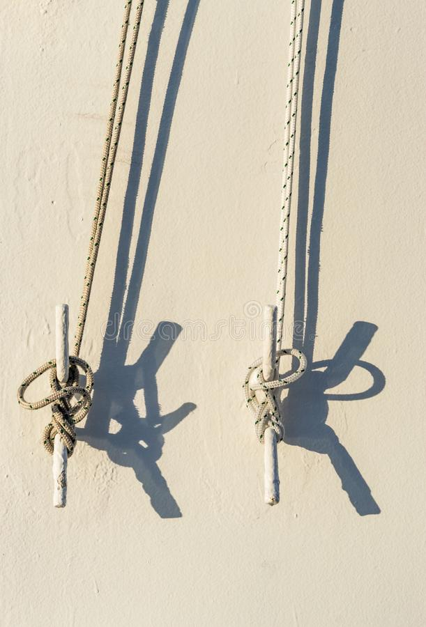 Two nautical ropes tied to metal cleats on wall of cruise ship. Two nautical ropes tied with marine knots to metal cleats on white exterior wall of cruise ship royalty free stock photography