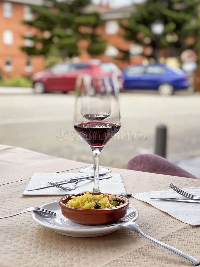 Two near glasses of red wine, bottle of wine and chef`s compliment, small plate of paella served on table outdoor stock image