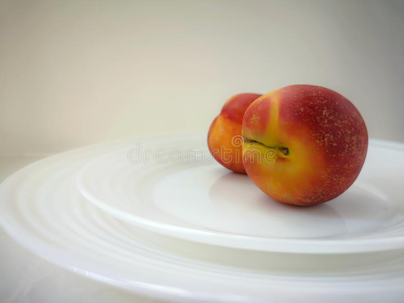 Two nectarines lie on two graceful white plates, set one on another. royalty free stock photo