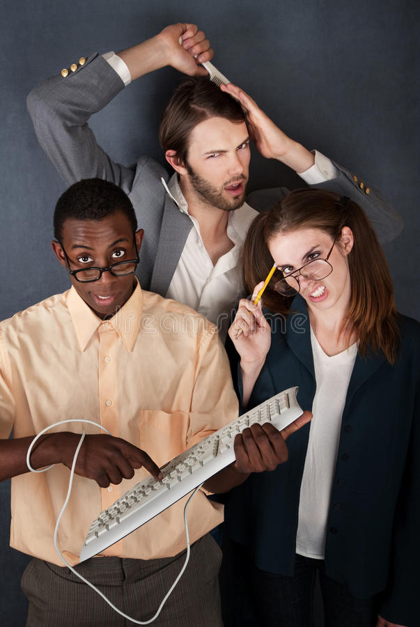Two Nerds and a Hipster. African-American and Caucasian geeks make faces while another man combs his hair royalty free stock images