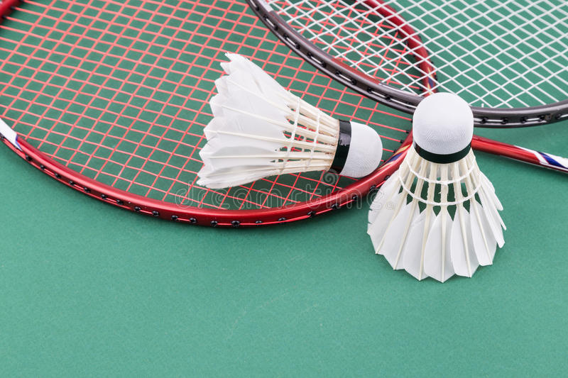 Two new badminton shuttlecock with rackets on green mat court. Two new badminton shuttlecock and rackets on green mat PVC court stock photo