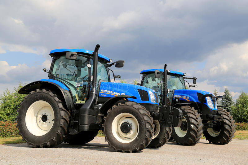 Two New Holland Agricultural Tractors. SALO, FINLAND - AUGUST 9, 2014: New Holland agricultural tractors T6.165 and T7.185 on display. New Holland Celebrates 50 royalty free stock images