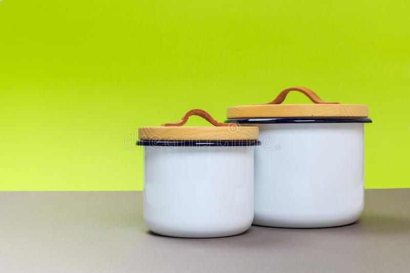 Two new metal saucepans with wooden lids on a gray table and a green background royalty free stock photos
