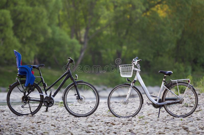 Two new modern bicycles :black with blue plastic child seat and white with basket standing on lit by sun pebbles on blurred green stock image