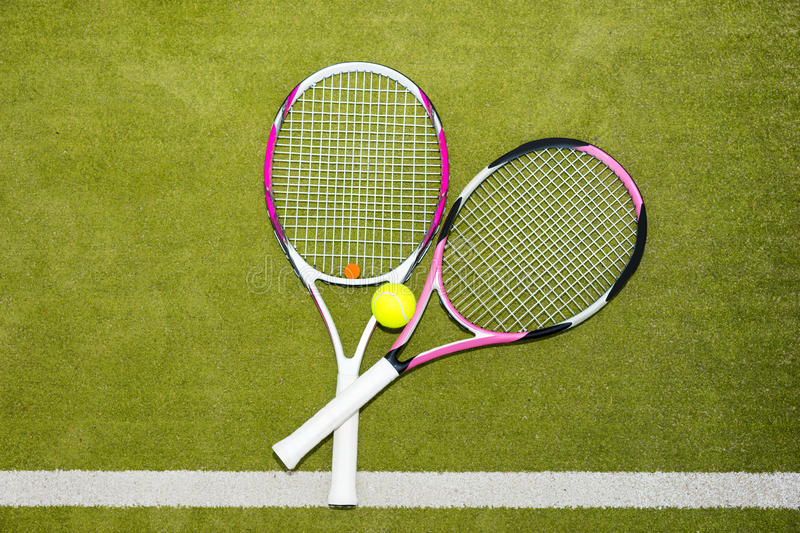 Two new pink tennis rackets with a tennis ball on a green grass royalty free stock photography
