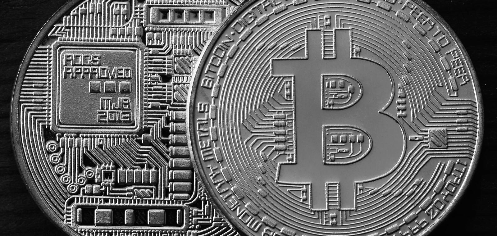 Two new silver physical bitcoins lies on dark wooden backgound, close up. High resolution photo. Cryptocurrency mining concep stock images