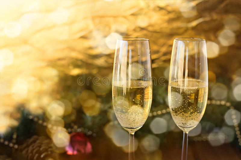 Two New Year`s glasses with champagne wine on a wooden table and stock image