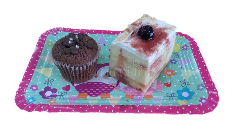 Two nice and delicious cakes on a colorful paper plate royalty free stock photography