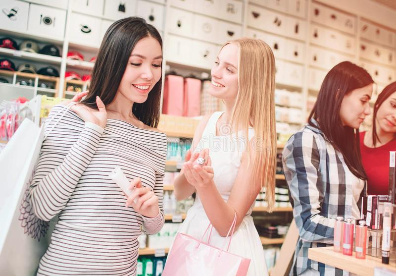 Two nice girls in the front are standing and smiling. Asian girl is looking at cosmetics that blinde girl has in her royalty free stock images