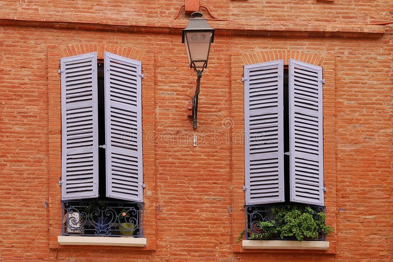Two nice windows on the brick wall with window sha. Windows on the red brick wall royalty free stock images