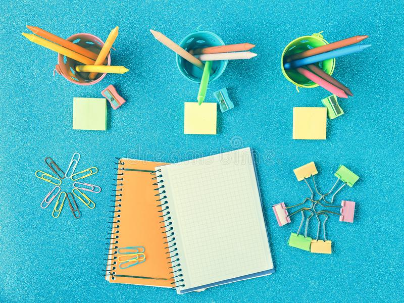 Two notebooks on blue background with colored pencils and school supplies. Multicolored background with school supplies and notebooks royalty free stock image