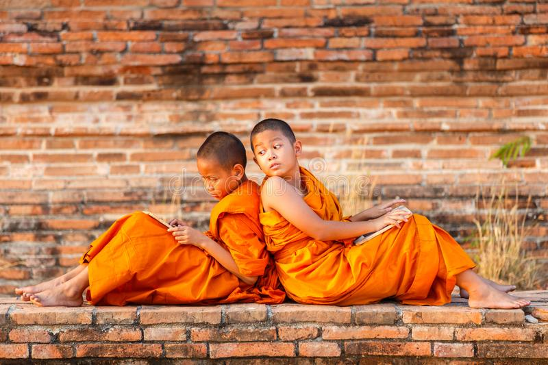 Two novice reading and studying blackboard with funny in old temple at sunset time. Ayutthaya Province, Thailand royalty free stock photo