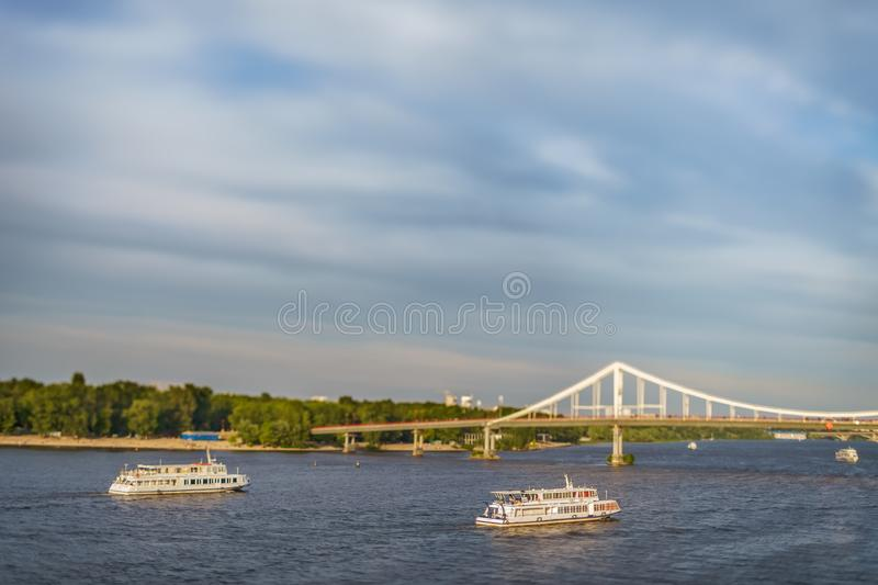 Two observing motor ships float down the river Dnieper. In windy weather, near the pedestrian bridge on Trukhanov the island, in the capital of Ukraine, the stock photos
