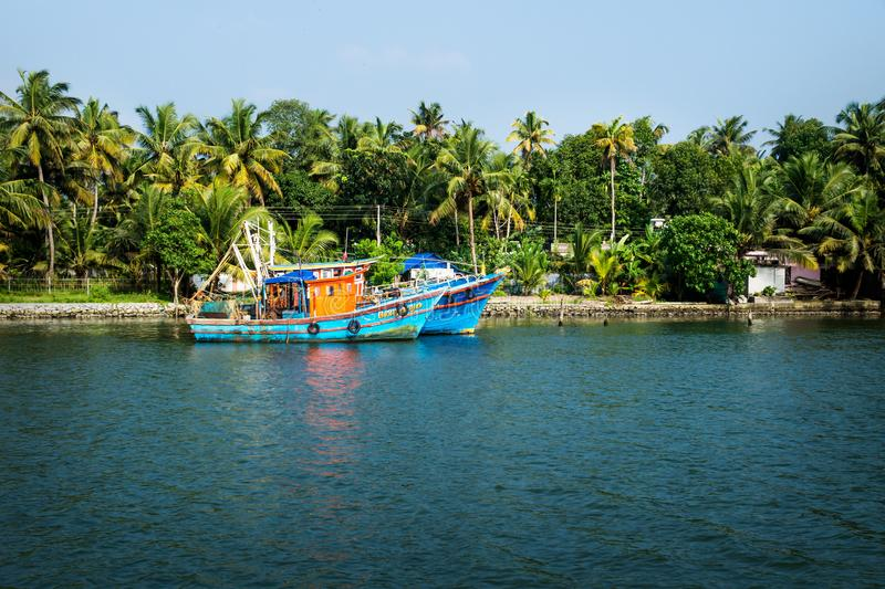 Two ocean fishing boats along the canal Kerala backwaters shore with palm trees between Alappuzha and Kollam, India. Two ocean fishing boats along the canal royalty free stock image