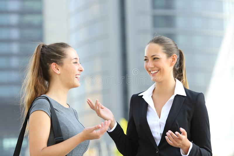 Two office employees talking in the street stock photography