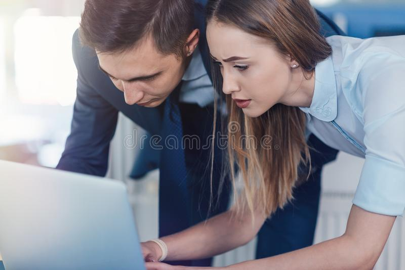 Collaboration. Two office workers men and women looking at the monitor close-up royalty free stock photo