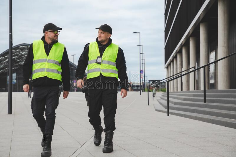 Two officers in reflective vests patrol the streets of the city royalty free stock photography