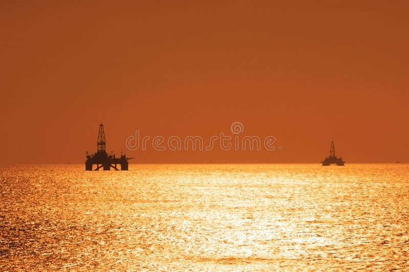 Two offshore oil rigs during s. Unset in Caspian sea stock photos
