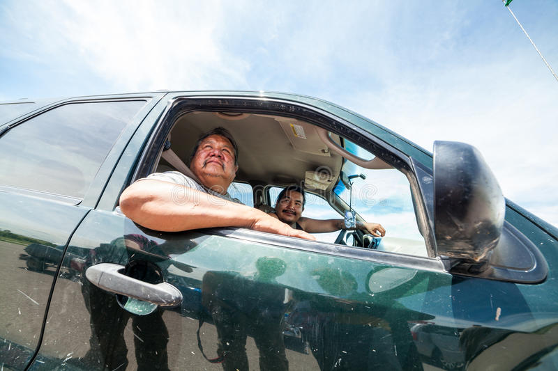 Two of Oglala native americans driving through Pine Ridge Indian. PINE RIDGE INDIAN RESERVATION, SD, USA - JULY 1, 2014: Two of Oglala native americans driving stock photography