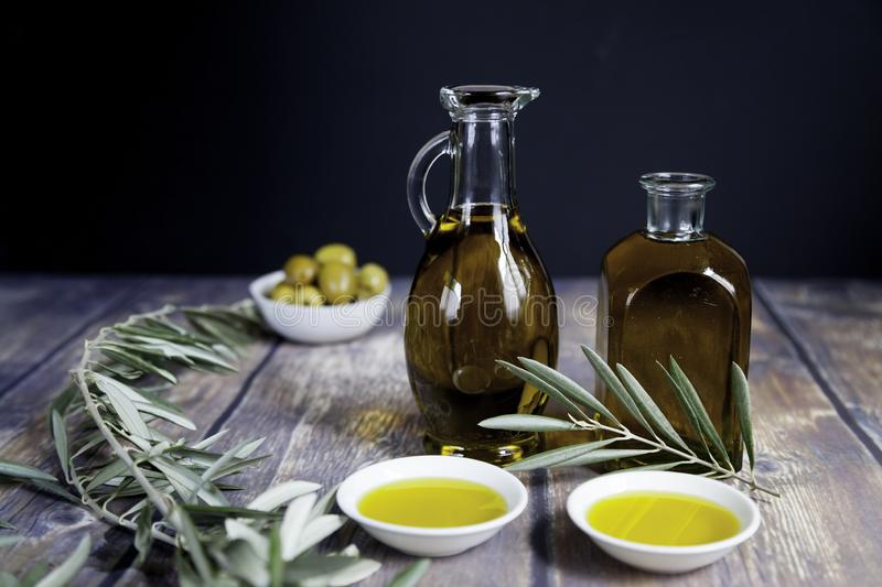 Two oil bottles and olive branch on black royalty free stock photos