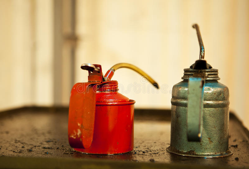 Two Oil Cans. Two cans of machine oil, one red and one green, rest on top of an old piece of greasy machinery that was used to make ammunition at the Ayalon stock photo