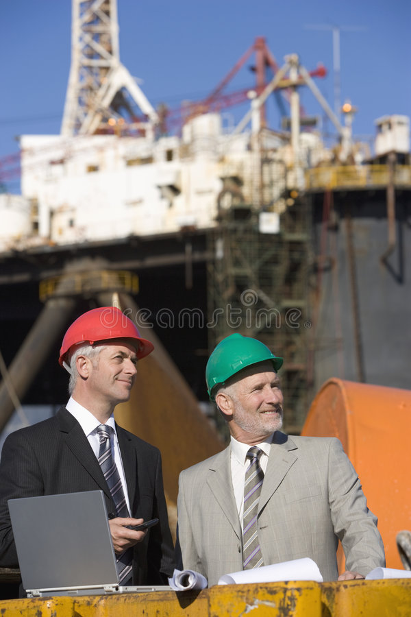 Two oil platform inspectors with a laptop. With the platform in the background royalty free stock photography