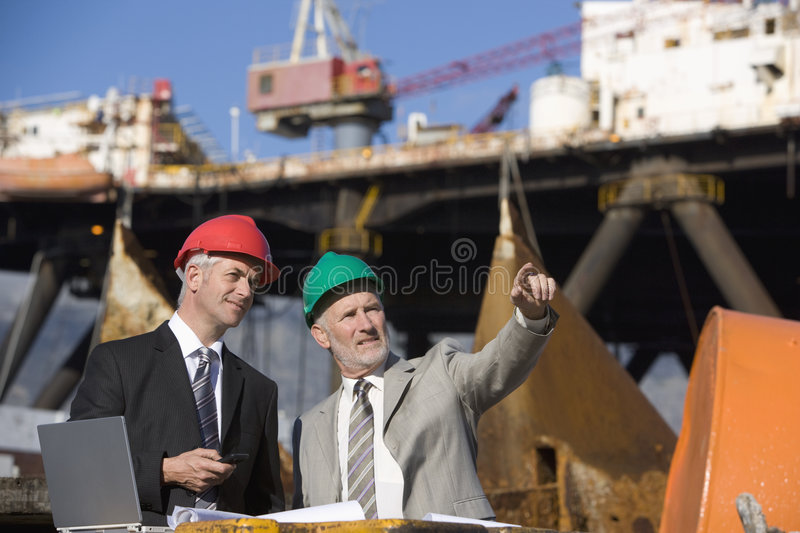 Two oil platform inspectors with a laptop. With the platform in the background royalty free stock photo