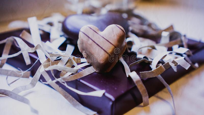 Two chocolate hearts on a purple background. royalty free stock photography