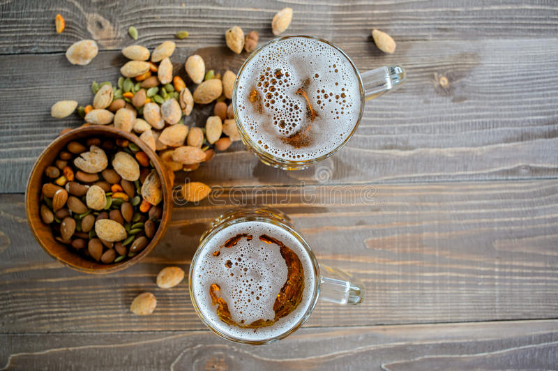 Two Oktoberfest beers with pistachio nuts on a wooden table. Top view stock images