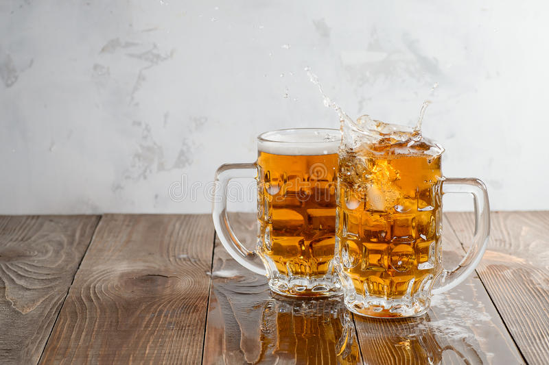 Two Oktoberfest beers splash on a wooden background. Two Oktoberfest beers splash on a wooden table stock photos