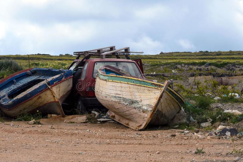 Two old abandoned fishing boats and a red wrecked car in a garbage dump. Abandoned things. Transport royalty free stock photo