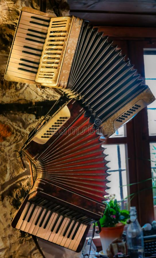 Two old accordions hanging on the wall stock photos